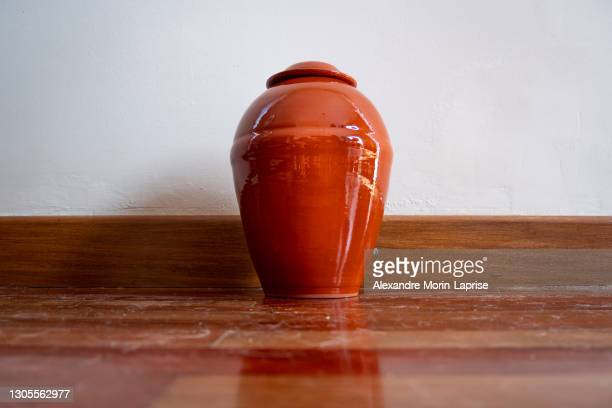 orange urn leaning against the white wall - cremation stock pictures, royalty-free photos & images