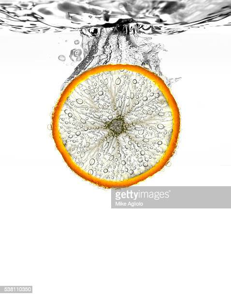 orange wedge being dropped into water - mike agliolo stock photos and pictures