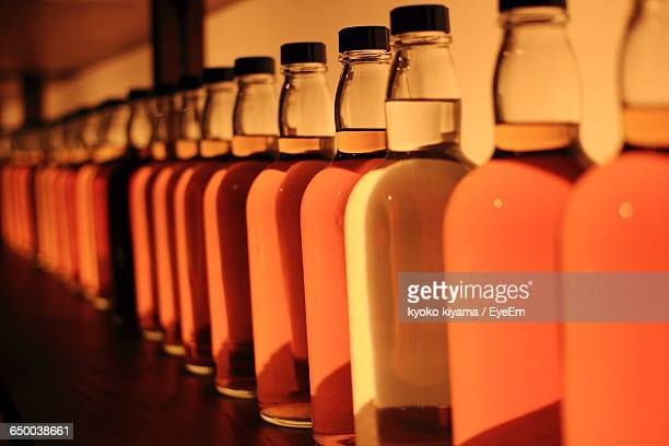Orange Whisky Bottles In Row On Table