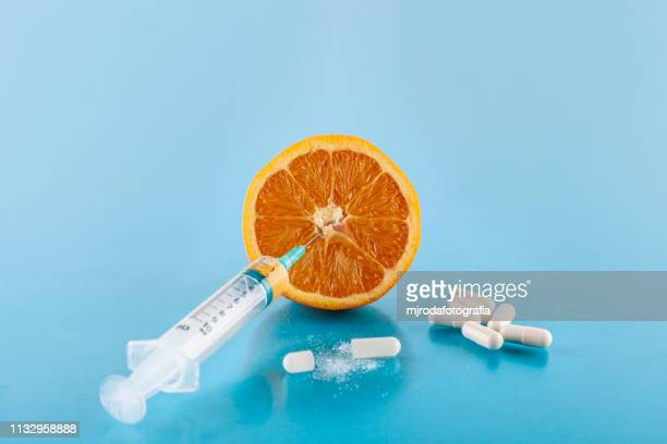 orange with a sringe stuck and spills - fruta stock photos and pictures