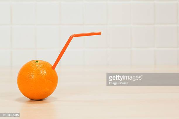 orange with drinking straw sticking out - convenience stock pictures, royalty-free photos & images