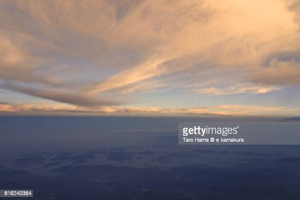 Orange-colored clouds on islands in Seto Inland Sea sunset time aerial view from airplane