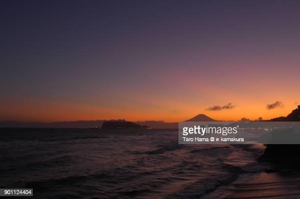 Orange-colored clouds on Mt. Fuji and Enoshima Island in Fujisawa city in Kanagawa prefecture in Japan after sunset