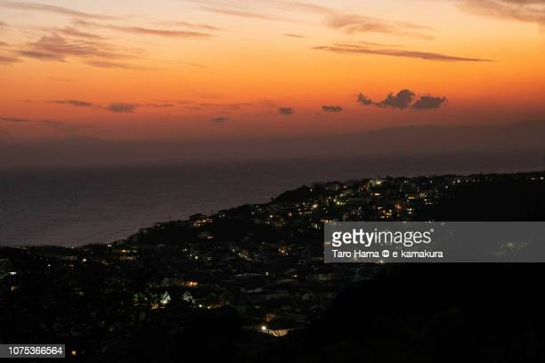 Orange-colored sunset sky and residential hill by the sea in Kamakura city in Kanagawa prefecture in Japan