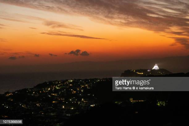 Orange-colored sunset sky, Enoshima Island and residential hill by the sea in Kamakura city in Japan