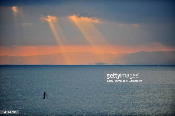 Orange-colored sunset sunbeam on Izu Peninsula, a paddle boarder on Sagami Bay, Northern Pacific Ocean in Japan