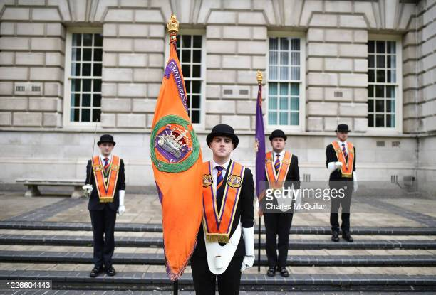 Orangemen observe social distancing as they take part in a wreath laying ceremony at Belfast City Hall on July 13, 2020 in Belfast, Northern Ireland....