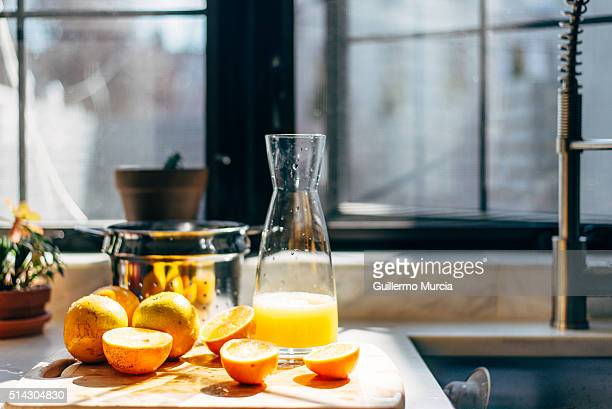 Oranges and carafe on a cutting board next to window