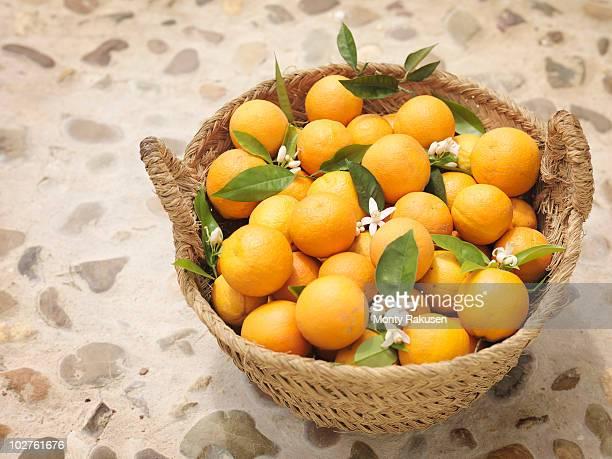 oranges and flowers in willow basket - monty rakusen stock-fotos und bilder