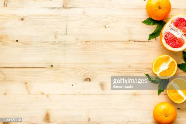 oranges grapefruits with leaves table top