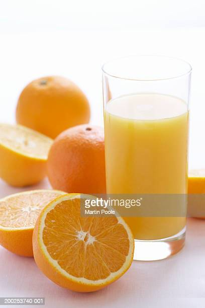 Oranges by orange juice in glass, close-up