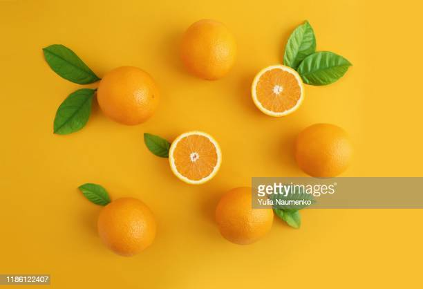 oranges fruits composition with green leaves and slice on yellow background, copy space. - zweifarbig farbe stock-fotos und bilder