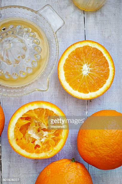 Oranges, halves of oranges and juice squeezer on grey wood, elevated view