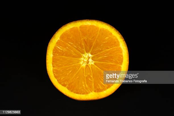 oranges on black background - orange grove stock photos and pictures