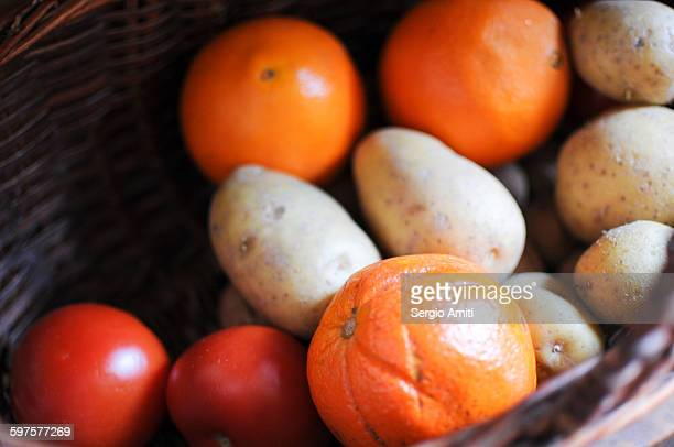 Oranges, potatoes and tomatoes in a basket