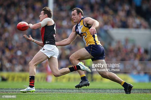 Orazio Fantasia of the Bombers handballs under pressure from Shannon Hurn of the Eagles during the round 11 AFL match between the West Coast Eagles...