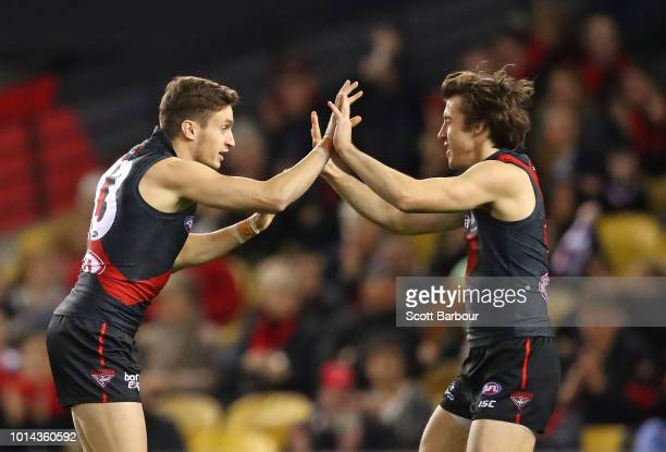 Orazio Fantasia of the Bombers is congratulated by Andrew McGrath of the Bombers after kicking a goal during the round 21 AFL match between the...
