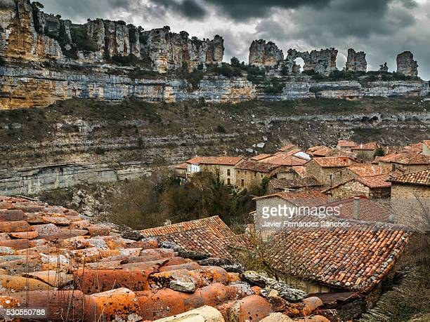 orbaneja del castillo. general view of the upper village with the roofs framed by spectacular rocks that contrasts on a stormy sky. burgos, spain. - orbaneja del castillo photos et images de collection