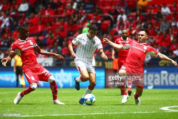 Orbelin Pineda of Chivas Cristian Borja and Antonio Rios of Toluca fight for the ball during the third round match between Toluca and Chivas as part...