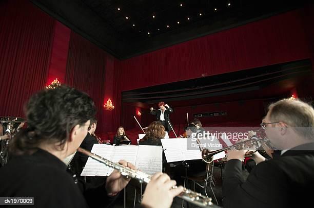 orchestra performing in a theatre - dirigent stock-fotos und bilder