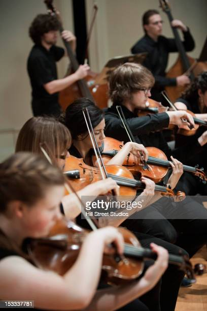 orchestra playing musical instruments together - violin family stock photos and pictures