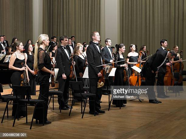 Orchestra standing at end of concert, conductor bowing