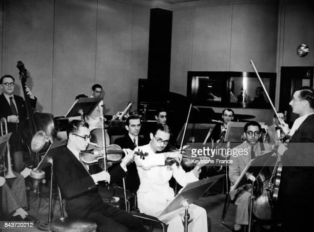 Orchestre d'une dizaine de musiciens jouant en direct dans un studio de la radio nationale avec en arrièreplan les techniciens du studio vus à...