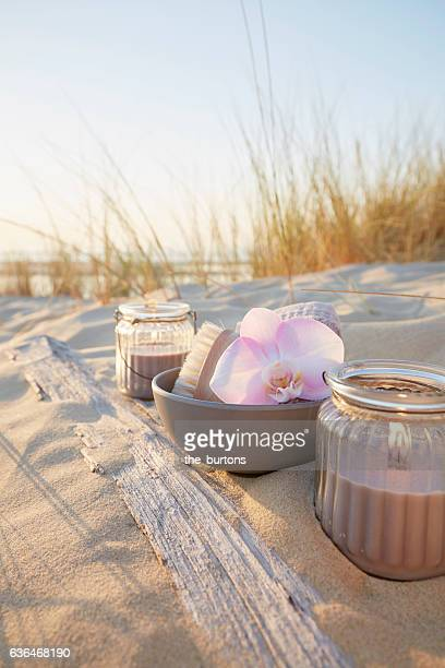 orchid in a bowl with candles and cosmetics on a sand dune, spa still-life