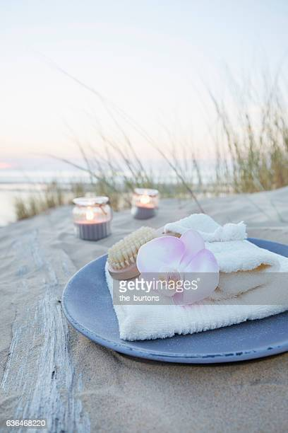 orchid on a plate with candles, towel and cosmetics on a sand dune, spa still-life