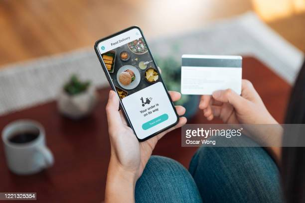 ordering food online at home with smartphone and credit card - take away food stock pictures, royalty-free photos & images