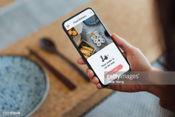 ordering food online at home with smartphone - food delivery foto e immagini stock
