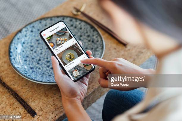 ordering food online at home with smartphone - portable information device stock pictures, royalty-free photos & images