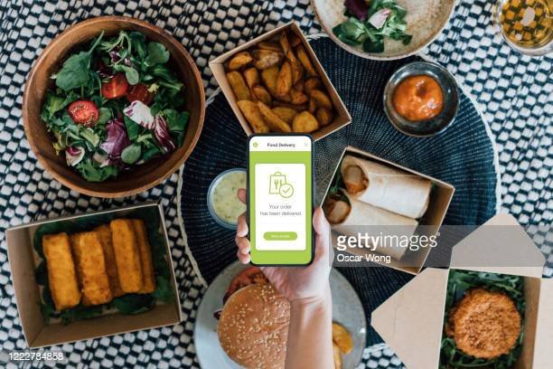 ordering takeaway meal online with smartphone - receiving stock pictures, royalty-free photos & images
