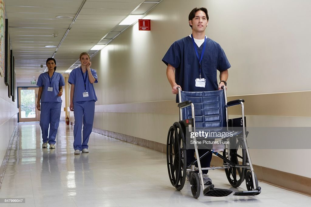 Orderly Pushing Wheelchair Down Hallway Stock Photo Getty Images