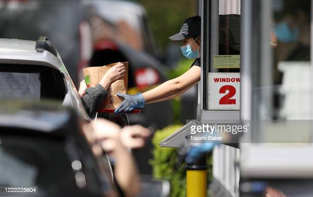 Orders are collected through a drive-through window as staff are seen wearing PPE equipment to hand over orders on a tray to minimize contact at the...