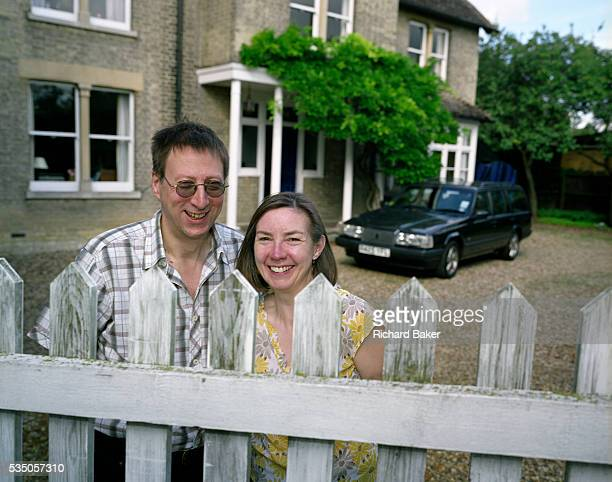 Ordinary husband and wife Mark and Christine Easterfield stand awkwardly at the dirty picket fence with their Volvo car parked on the gravel drive...