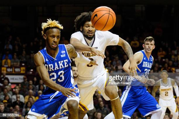 Ore Arogundade of the Drake Bulldogs and Jordan Murphy of the Minnesota Golden Gophers go after a loose ball during the game on December 11 2017 at...