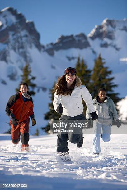 usa, oregon, bend, three young adults running in snow, smiling - man met een groep vrouwen stockfoto's en -beelden
