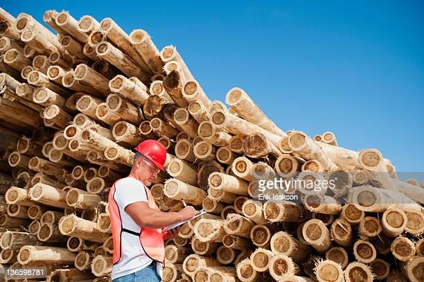 usa, oregon, boardman, engineer in front of stack of timber - baumaterial stock-fotos und bilder
