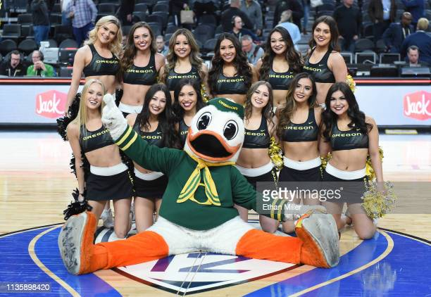 Oregon Ducks cheerleaders and mascot The Duck pose on the court after the team's 6654 victory over the Utah Utes in a quarterfinal game of the Pac12...
