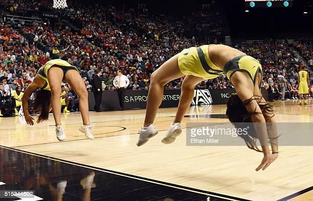 Oregon Ducks cheerleaders do backflips during the championship game of the Pac12 Basketball Tournament against the Utah Utes at MGM Grand Garden...