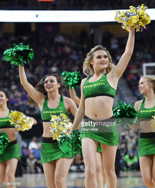 Oregon Ducks cheerleaders run off the court after performing during a semifinal game of the Pac12 basketball tournament against the Arizona State Sun...