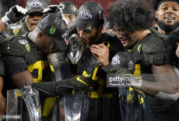 Oregon Ducks players celebrates with the Pac12 Championship Trophy after the Ducks defeated the Utah Utes 3715 in the Pac12 Championship Game at...