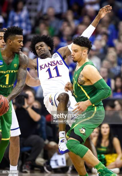 Oregon forward Dillon Brooks runs a screen on Kansas guard Josh Jackson in the second half during the NCAA Tournament's Midwest Region final at the...