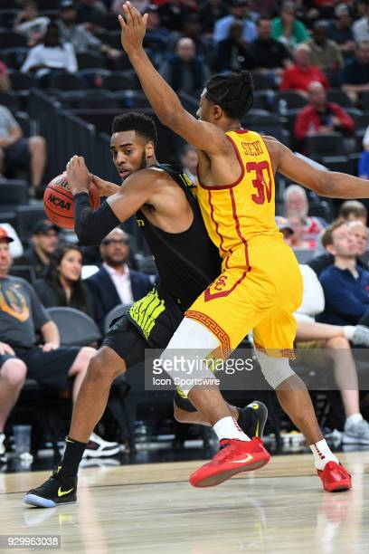 Oregon forward Troy Brown is closely defended by USC guard Elijah Stewart during the semifinal game of the mens Pac12 Tournament between the Oregon...