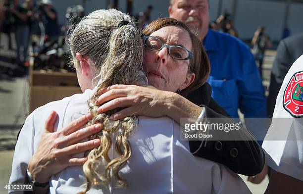 Oregon governor Kate Brown hugs Battalion Chief Teresa Mutschleras she was thanking first responders for their efforts yesterday at Umpqua Community...