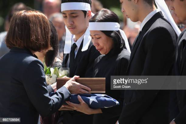 Oregon Governor Kate Brown presents Myhanh Best with an Oregon state flag during a committal service for her husband Ricky Best an Army veteran and...