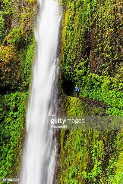 USA, Oregon, Hood River County, Columbia River Gorge, Eagle Creek Trail, Female tourist at Tunnel Falls