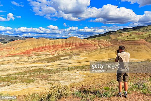 USA, Oregon, John Day Fossil Beds National Monument, tourist photograghing Painted Hills