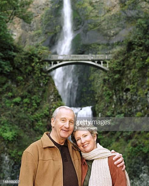 usa, oregon, mature couple smiling, multnomah falls in backgroun - multnomah falls stock photos and pictures